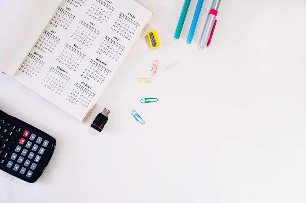 Agenda com canetas e calculadora